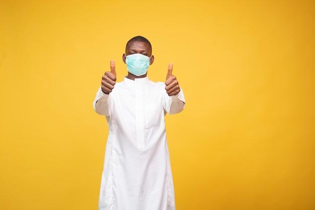 フェイスマスクを身に着けている若いアフリカのイスラム教徒の男性は、親指をあきらめる