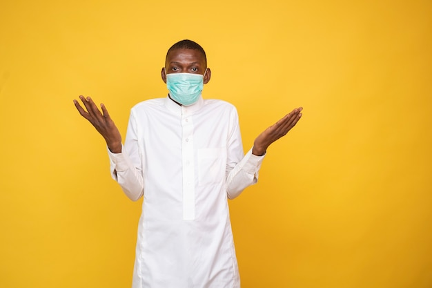 Young african muslim man wearing a face mask, shrugging