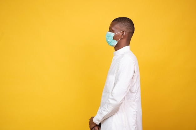 A young african muslim man wearing a face mask