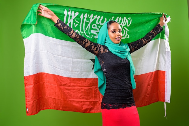 緑の壁とクロマキーに対して若いアフリカのイスラム教徒の女性