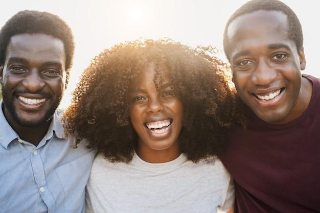 Молодые африканцы улыбаются перед камерой на улице в городе - сосредоточьтесь на лице девушки в центре