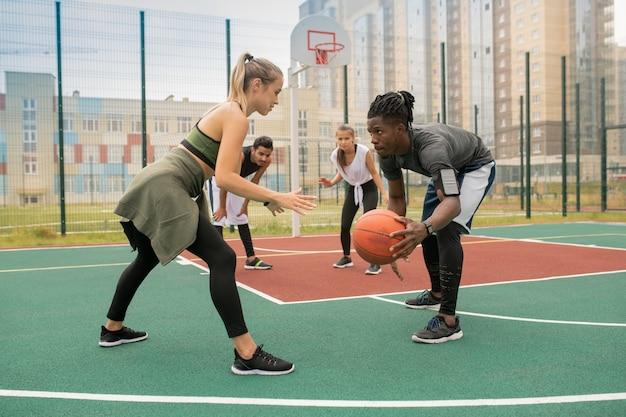 Молодой африканский игрок с мячом и белокурая спортсменка, стоящие на площадке напротив друг друга во время игры