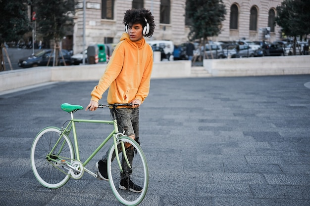 Молодой африканский всадник веселится, слушая музыку по городу - сосредоточьтесь на руках, держащих велосипед