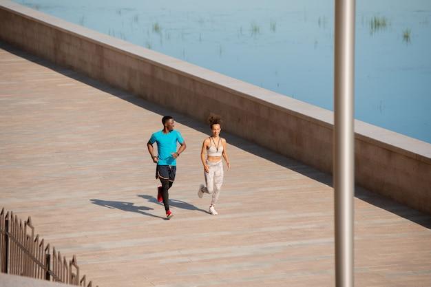 여름 아침에 훈련하는 동안 도시 환경에서 줄넘기로 점프하는 활동복을 입은 젊은 아프리카 스포츠맨