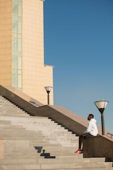 도시 환경에서 현대 건축 앞의 큰 계단으로 대리석 난간에 앉아 activewear에 젊은 아프리카 운동가