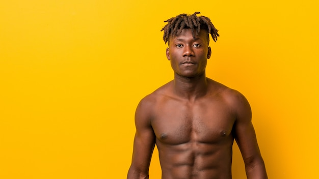 Young african sporty man standing against a yellow without t-shirt