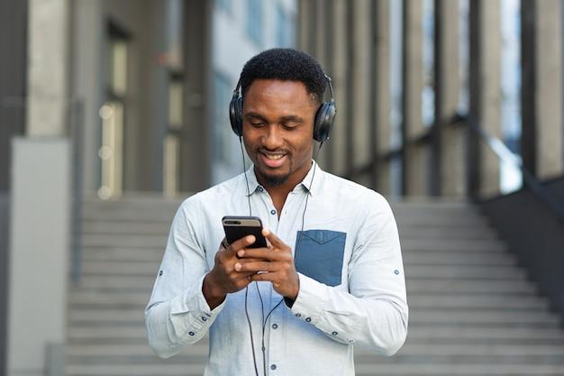 大きなヘッドホンを使ってスマートフォンから音楽を聴き、アプリを使う便利さから笑顔の若いアフリカの学生