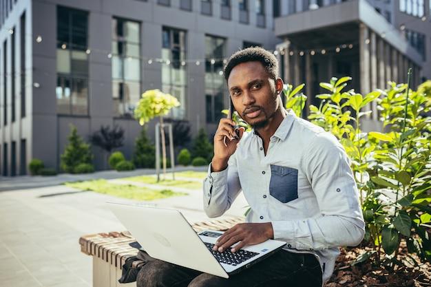 Молодой африканский студент учится онлайн, сидя на скамейке возле университета, использует ноутбук и смартфон