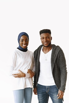 Young african students couple. woman wearing traditional sudan muslim hijab. isolated on white backgound