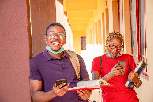 Young african students feeling excited using their mobile phones, wearing face masks, new normal