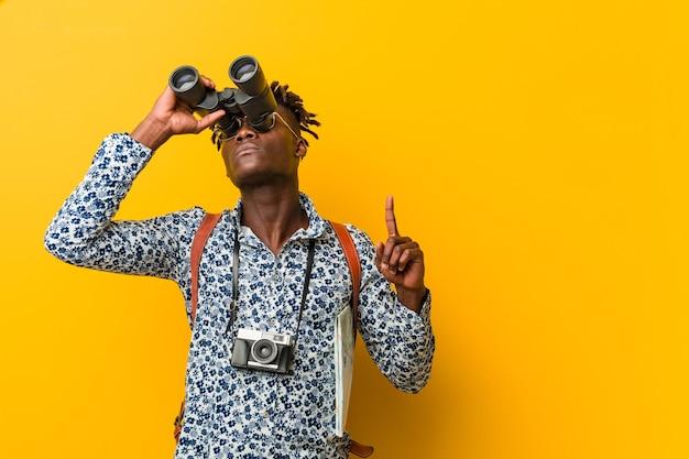 쌍안경을 들고 노란색 배경에 서있는 젊은 아프리카 관광 남자