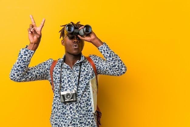 双眼鏡を保持している黄色の背景に立っている若いアフリカの観光人
