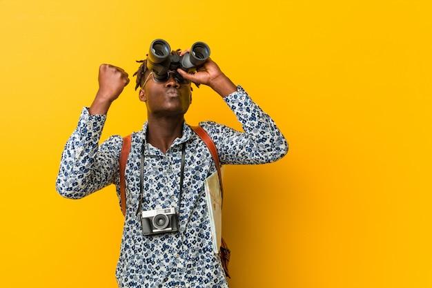 双眼鏡を保持している黄色の壁に立っている若いアフリカ観光客の男