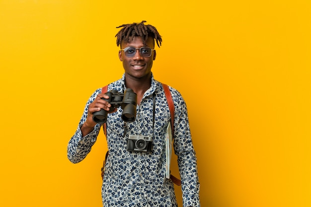 Young african tourist man standing against a yellow background holding a binoculars