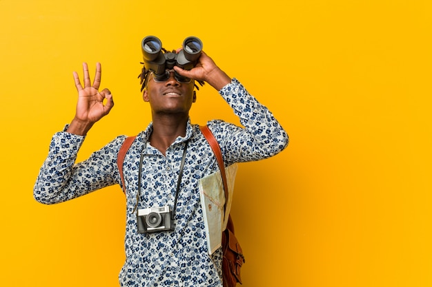 Young african tourist man standing against a yellow  holding a binoculars
