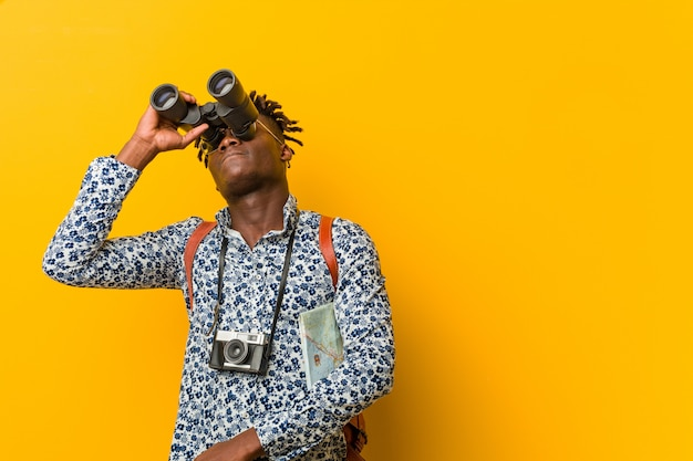 Young african tourist man standing against a yellow wall holding a binoculars