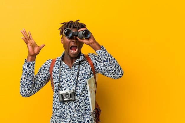 双眼鏡を保持している黄色の上に立っている若いアフリカ観光男