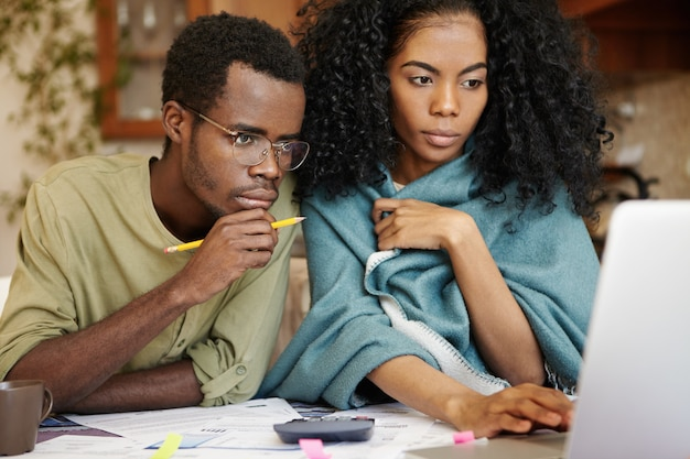 Young african wife and husband with many debts doing paperwork together, analyzing expenses, planning family budget and calculating bills, sitting at kitchen table with laptop, calculator and papers