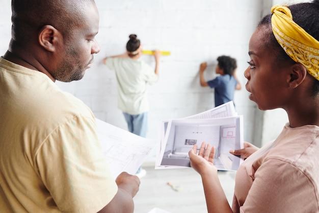 若いアフリカの女性と彼女の夫は、壁のそばに立っている2人の子供たちの前でリビングルームのドラフトとインテリアで書類について話し合っています