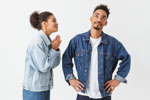 Young african woman apologizes to the her boyfriend over grey wall