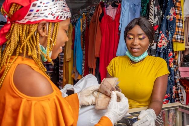 현지 상점에서 지불하기 위해 돈을 세는 젊은 아프리카 여성