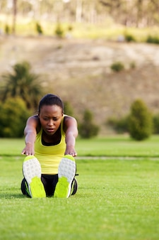 Young african woman doing stretching exercise at park