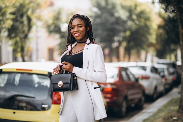 Young african woman dressed in white suit outside the street