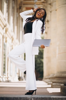 Young african woman dressed in white using laptop