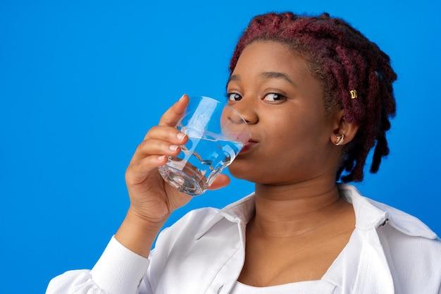 青い背景のガラスから水を飲む若いアフリカの女性