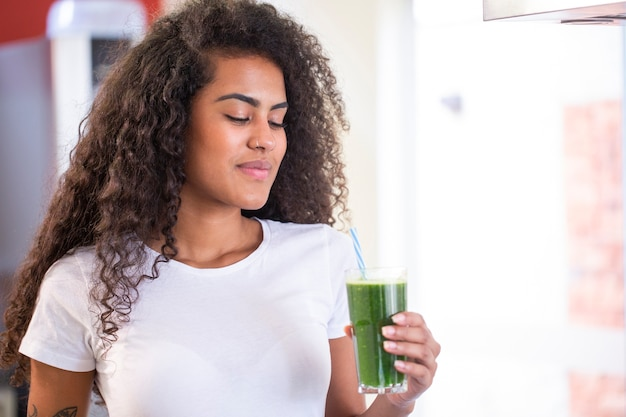 젊은 아프리카 여성은 체중 감소와 해독을위한 건강한 채식 스무디를 즐길 수