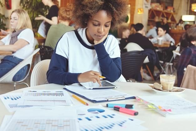 Молодая африканская женщина-предприниматель с серьезным сосредоточенным выражением лица сидит в коворкинг-кафе с компьютером и бумагами с сенсорной панелью, анализирует финансовую информацию на планшете, положив локоть на стол