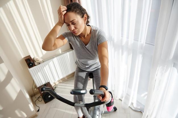 Молодая африканская женщина чувствует себя истощенной после тренировки на велотренажере