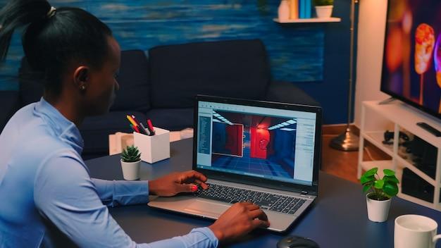 늦은 밤 집에서 노트북으로 온라인 프로 게임을 테스트하는 젊은 아프리카 여성 게이머. 현대 기술 네트워크 무선으로 컴퓨터에서 디지털 비디오 게임을 확인하는 프로 선수.