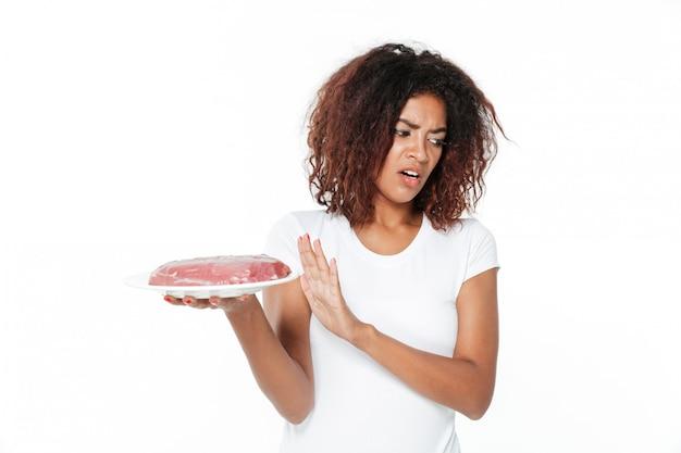 肉を保持している若いアフリカ人女性。