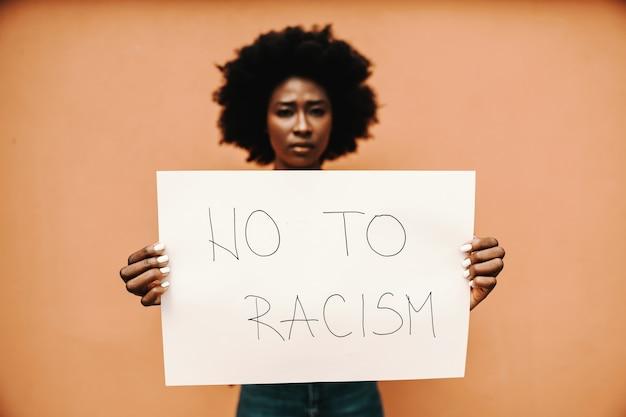 人種差別のタイトルがない紙を保持している若いアフリカの女性。