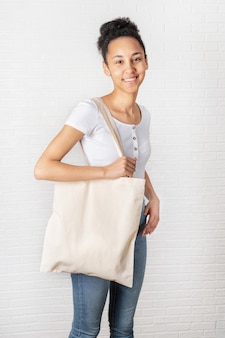 Young african woman holding white eco bag