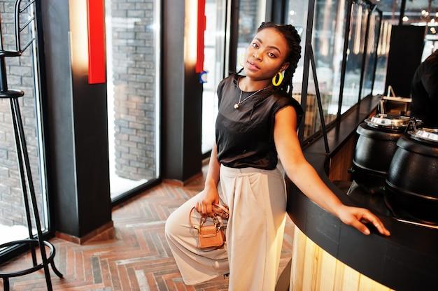 カフェで黒いブラウスを着た若いアフリカの女性。
