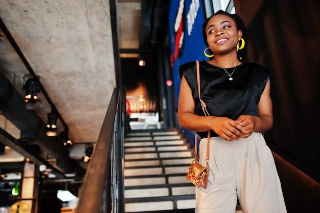 カフェで黒いブラウスを着た若いアフリカの女性。 Premium写真