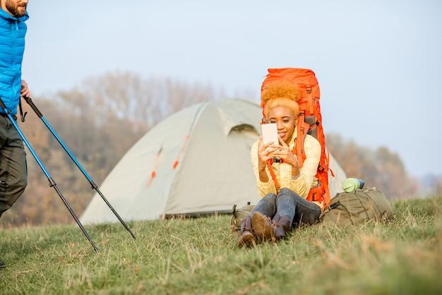 キャンプ場の近くの緑の芝生に座ってスマートフォンを楽しんでいるバックパックとカラフルなジャケットの若いアフリカの女性