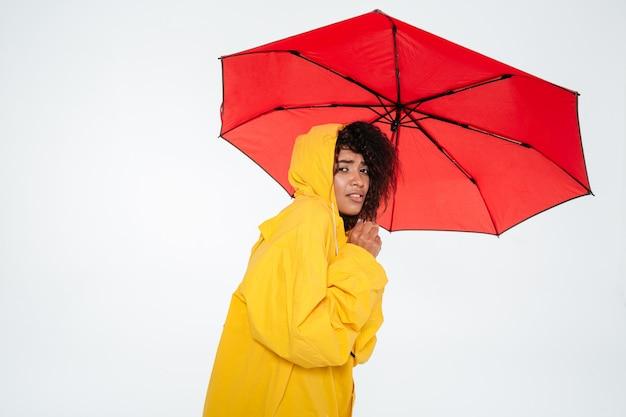 傘の後ろに隠れているレインコートの若いアフリカ人女性