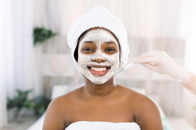 若くて美しい肌とリラクゼーションのためのさわやかな顔のマスクでボディケアを行うスタジオで若いアフリカ人女性