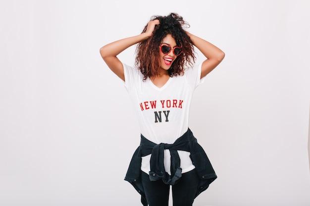 サングラスとデニムジャケットを着た流行のtシャツを着た若いアフリカの女性。手を上げてポーズをとりながら、楽しんでいる巻き毛の短い髪のスリムな女の子を笑っています。
