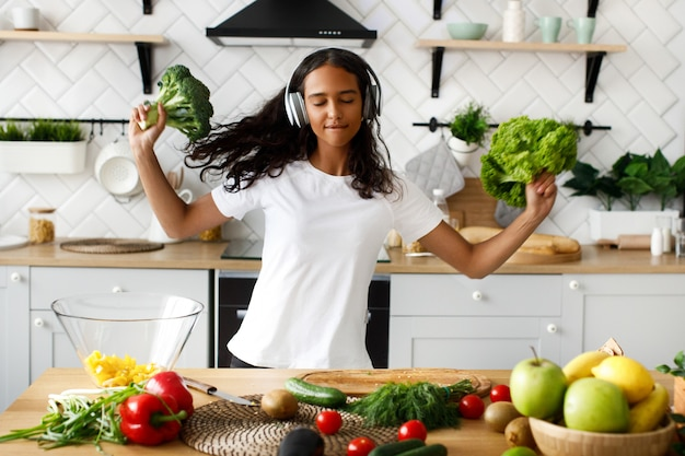 Young african woman is happy listening to music via headphones with closed eyes and holds a broccoli and salad