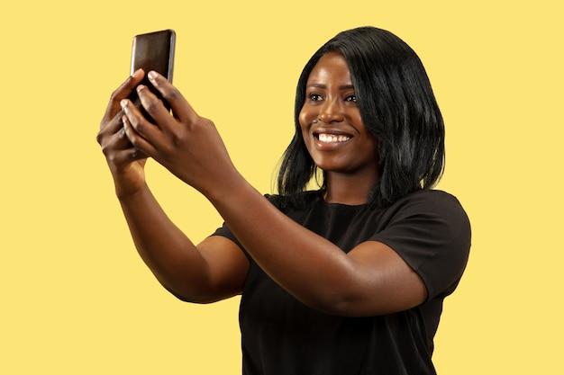 노란색 스튜디오 배경, 표정에 고립 된 젊은 아프리카 여성