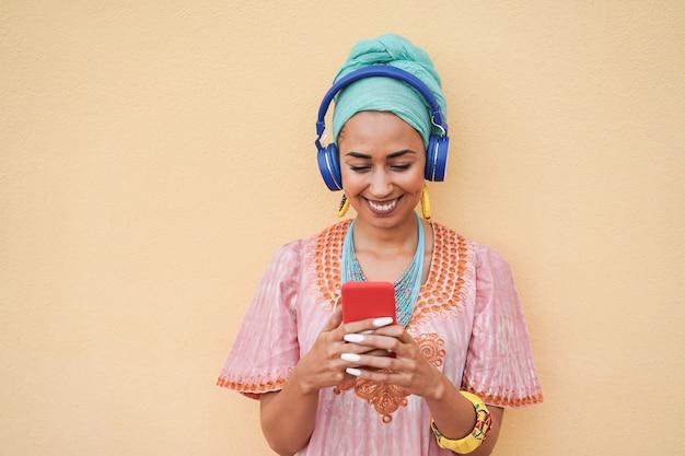 Молодая африканская женщина слушает музыкальный плейлист, глядя на мобильный телефон - сосредоточьтесь на лице