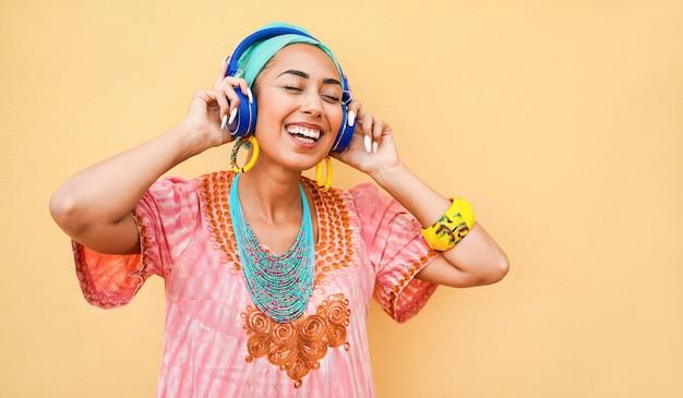 Молодая африканская женщина, слушающая музыку с устройством наушников - счастливая женщина с удовольствием танцует и поет на открытом воздухе - образ жизни, стильный и технологичный концепт