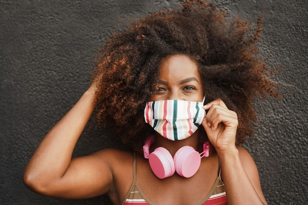 Young african woman listening music with headphones - focus on face
