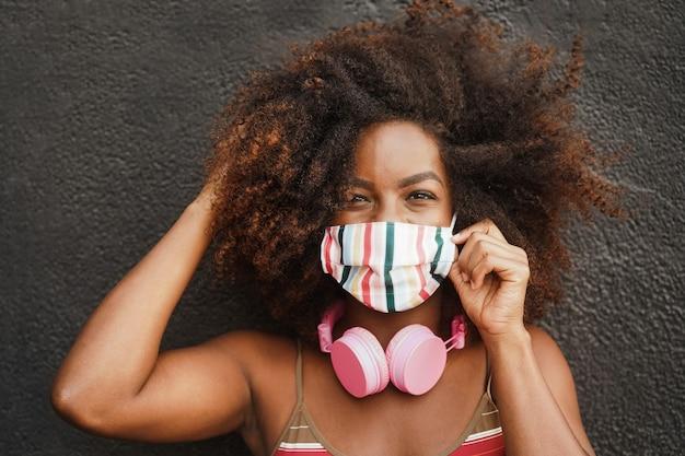 Молодая африканская женщина слушает музыку в наушниках - сосредоточиться на лице