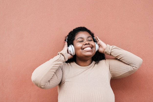 Young african woman listening music with headphones outdoors in the city - focus on face