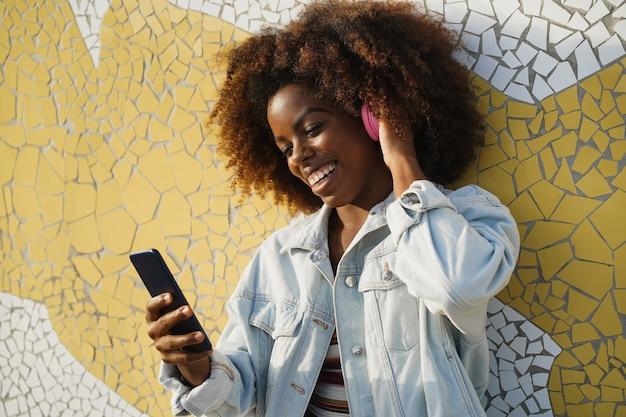 街の屋外でヘッドフォンで音楽を聴く若いアフリカの女性-顔に焦点を当てる